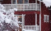 Mökki lumisateessa